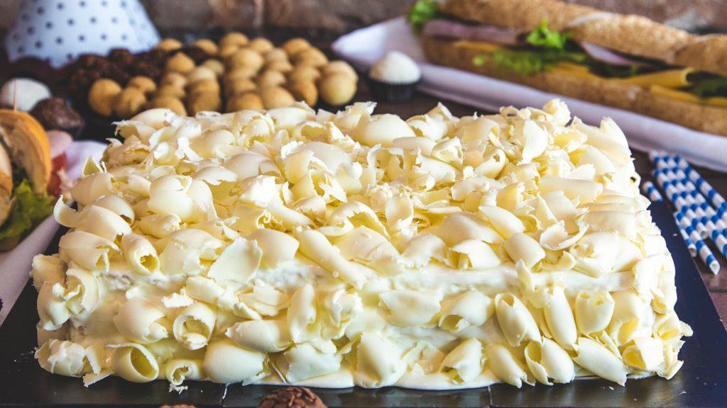 Bolo confeitado de Leite Ninho com raspas de chocolate branco